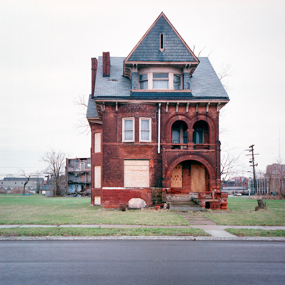 Vacant, red brick residence on isolated lot in Detroit neighborhood